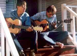 John Herman and Skip Reising play guitar on a porch in Seattle in 1969.  Bill Yenne photographed them when they had time off from working on the crabbing boat.